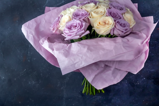 Bouquet of fresh amazing white and purple roses in craft paper on dark background