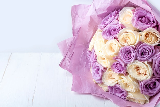 Bouquet of fresh amazing white and purple roses in craft paper on white background for postcard, cover, banner.