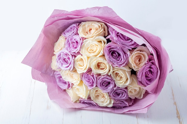 Bouquet of fresh amazing white and purple roses in craft paper