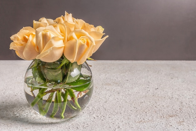 Bouquet of fresh beige roses in a vase. the festive concept for weddings, birthdays, march 8th, mother's, or valentine's day. greeting card, dark background
