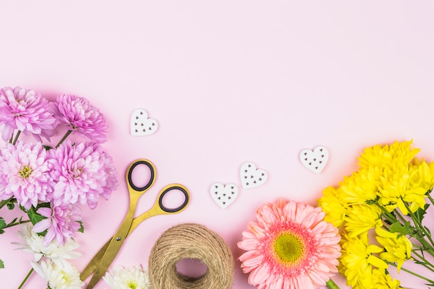 Bouquet of fresh flowers near scissors and ornamental hearts