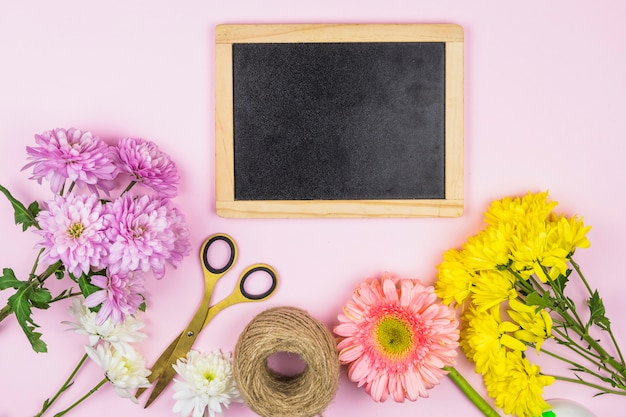 Bouquet of fresh flowers near scissors and photo frame