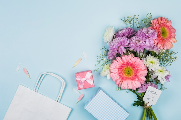 Bouquet of fresh flowers with title on tag near packet, present and notebook
