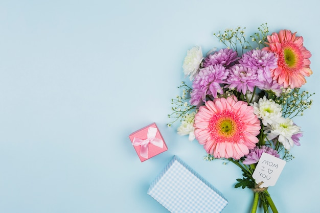 Bouquet of fresh flowers with title on tag near present box and notebook