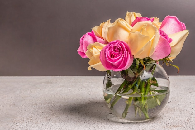 Bouquet of fresh multicolored roses in a vase. the festive concept for weddings, birthdays, march 8th, mother's, or valentine's day. greeting card, dark background