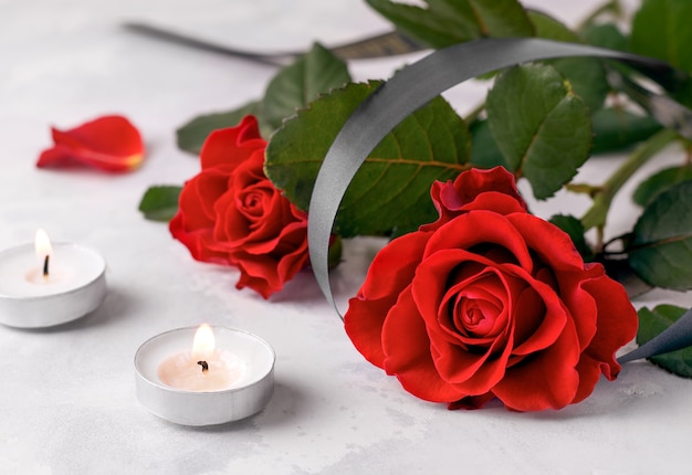 Bouquet of fresh red roses next to two mourning candles