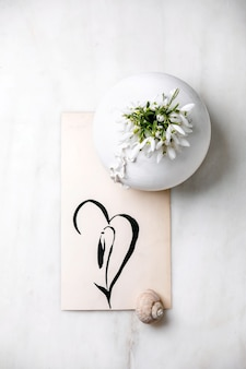 Bouquet of fresh snowdrops spring flowers in white porcelain vase with snail shell and hand drawn snowdrop on white marble table. spring time composition