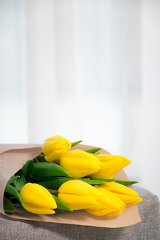Bouquet of fresh tulips yellow color on gray armchair near tulled window in home interior