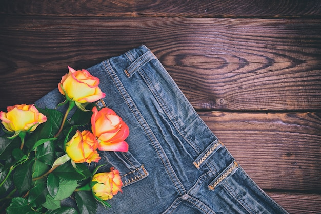Bouquet of fresh yellow roses lying on the blue jeans