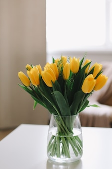 Bouquet of fresh yellow tulips on a table in living room interior
