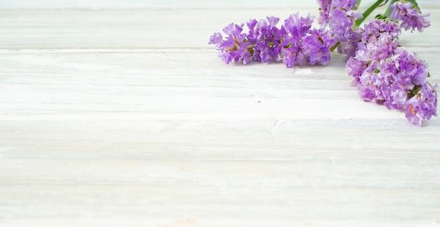 白い木製のテーブルに紫のスターチス花から花束