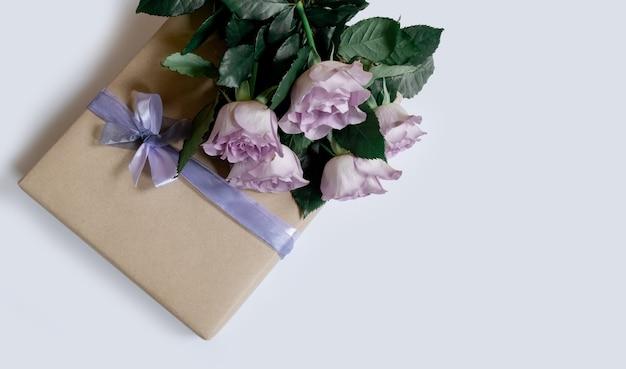 흰색 배경에 선물 상자가 있는 보라색 장미 꽃다발, 위쪽 전망, 복사 공간.