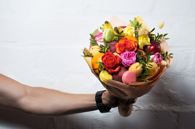 A bouquet of fruits and flowers is given by a man on a white background