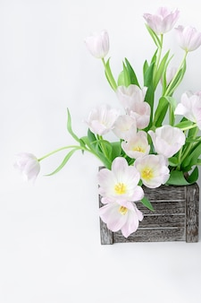 A bouquet of gently pink tulips in a wooden box on a white background.