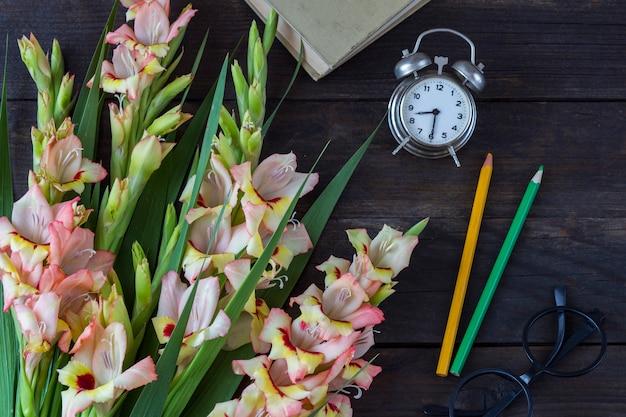A bouquet of gladioli, a book, a pencil, glasses, an alarm clock