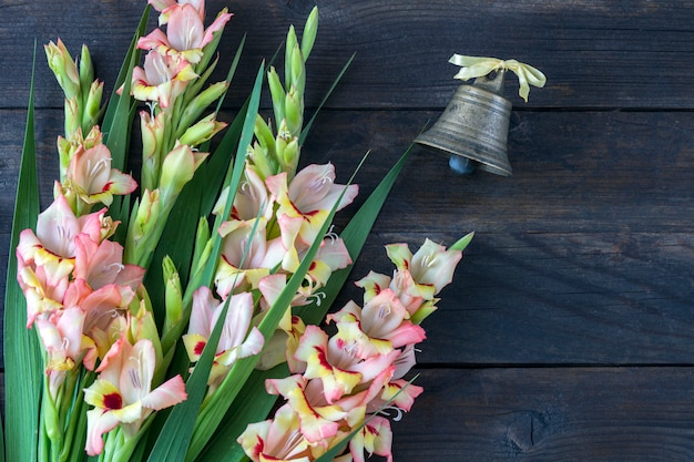 A bouquet of gladiolus and the old bell