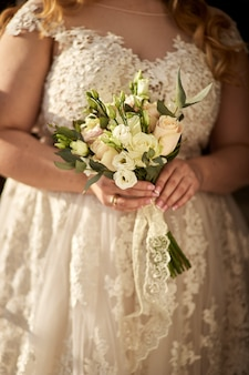 Bouquet in hands of the bride, woman getting ready before wedding ceremony