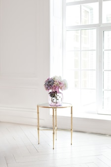 Bouquet of hydrangeas in a glass vase in a luxurious interior by the window. a bouquet of flowers on a table in a white room at home. the classic interior of the living room. home decor. scandinavia.