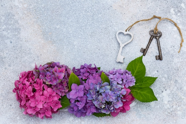 A bouquet of hydrangeas and keys on a light background