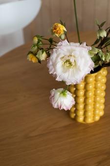黄色のセラミックデザイナー花瓶の花束。それはテーブルの上です 。