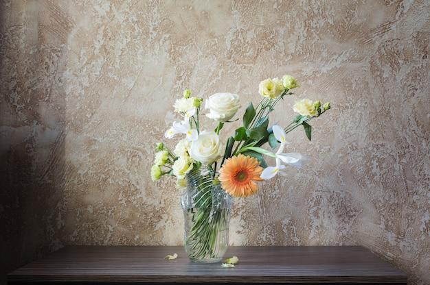 배경 벽에 있는 테이블에 유리 꽃병에 꽃다발