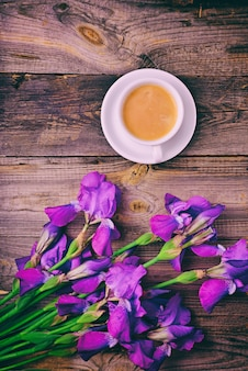 Bouquet of irises and a cup of coffee