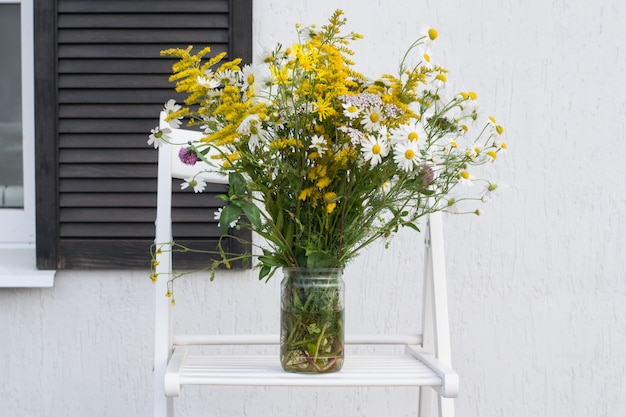 Bouquet in jar on background of house white wall