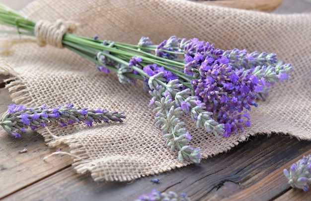 Bouquet of lavender flowers on piece of fabric on  wooden table