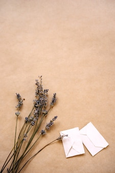 A bouquet of lavender and two small handmade envelopes on craft paper for packaging.