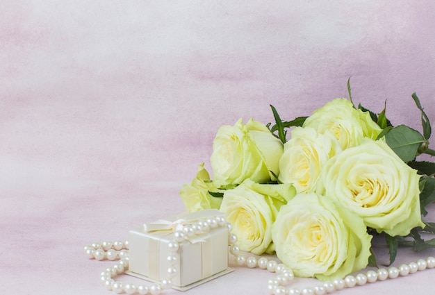 Bouquet of light roses, gift box and pearl beads on a pink background