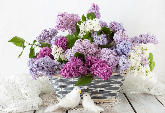 A bouquet of lilac in a basket on a wooden table and two white doves