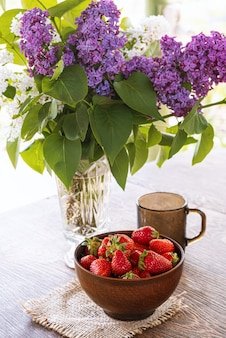 Bouquet of lilac branches in crystal vase, clay bowl with red strawberry and dark glass cup on wooden table.