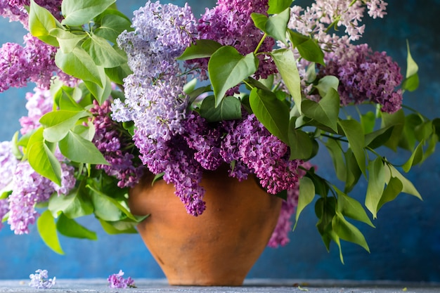 Bouquet of lilac in a clay vase on a dark blue textured