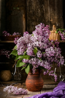 Bouquet of lilac flowers in a ceramic pot on old table