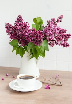 Bouquet of lilac flowers in a vase and cup of coffee on a wooden table.