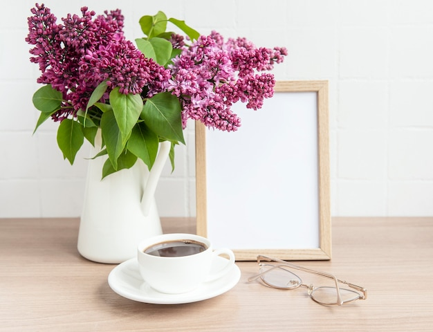 Bouquet of lilac flowers in a vase and empty frame on a wooden table. Premium Photo