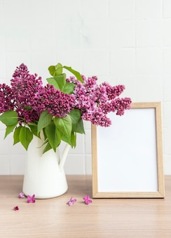 Bouquet of lilac flowers in a vase and empty frame on a wooden table.