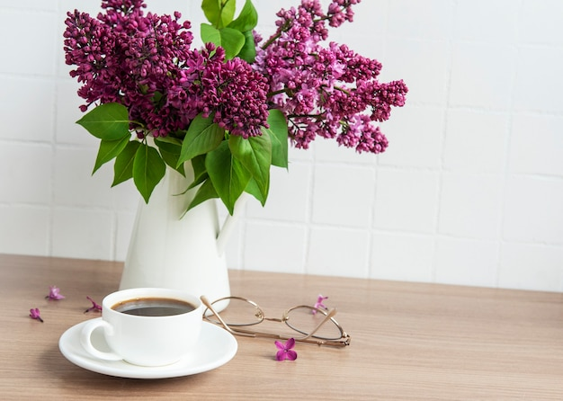Bouquet of lilac flowers in a vase  on a wooden table.