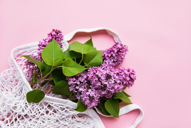 Bouquet of lilac in reusable shopping eco mesh bag on pink surface