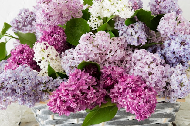 A bouquet of lilac in a white basket close up