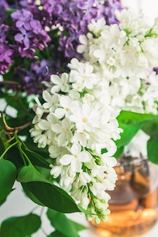 A bouquet of lilac and white lilac flowers in a glass vase near the location