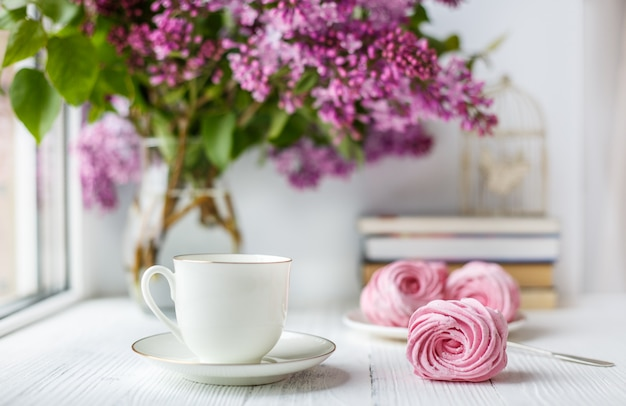 Bouquet of lilacs, cup of coffee, homemade marshmallow. romantic spring morning