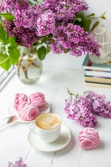 Bouquet of lilacs, cup of coffee, homemade marshmallow. romantic spring morning.