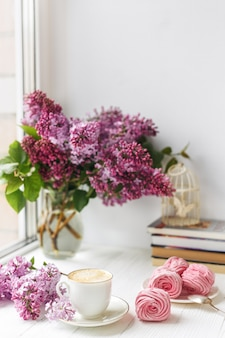 Bouquet of lilacs, cup of coffee, homemade marshmallow and stack of books on window sill romantic spring morning.
