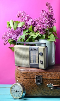Bouquet of lilacs in enameled kettle on antique suitcase, vintage radio, alarm clock on  pink background. retro style still life