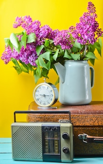 Bouquet of lilacs in enameled kettle on antique suitcase, vintage radio, alarm clock on yellow background. retro style still life