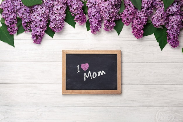 A bouquet of lilacs with chalk board on white boards . mother's day