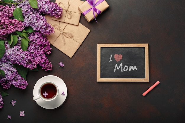 A bouquet of lilacs with cup of tea, chalk board, gift box, craft envelope, a love note on rusty background . mother's day