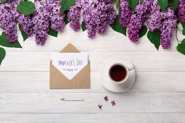 A bouquet of lilacs with cup of tea, craft envelope and a love note on white boards . mother's day