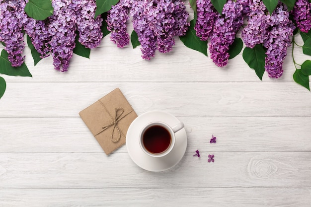A bouquet of lilacs with cup of tea and craft envelope on white boards . mother's day